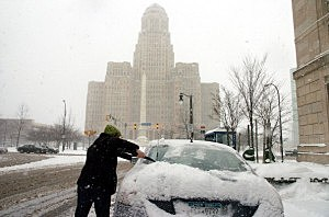 man cleaning off his car in front of Buffalo City Hall