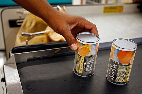 cans of juice on a conveyer belt