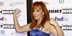 Country singer McEntire flexes as she arrives at the Muhammad Ali Celebrity Fight Night awards banquet in Scottsdale