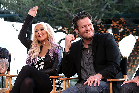 Blake Shelton sitting next to Christina Aguilera