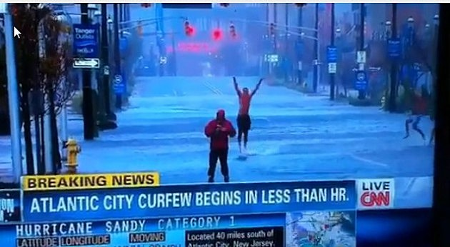 Reporter in the middle of a hurricane with a guy jumping up and down behind him