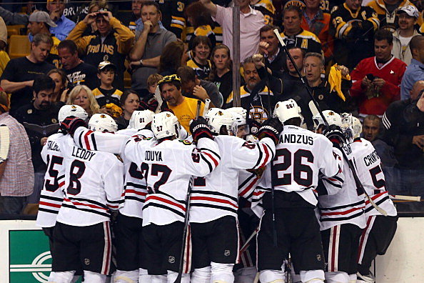 Brent Seabrook #7 of the Chicago Blackhawks celebrates with teammates after scoring the game winning goal in overtime
