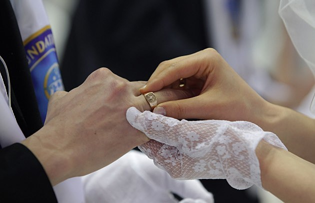 woman putting a ring on a man
