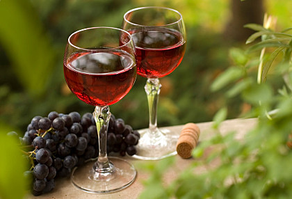 red wine in glass with red grape close up