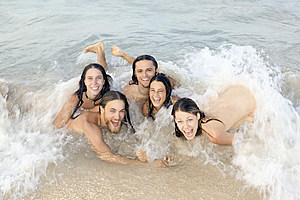 A group of nude young people smile at the viewer while skinny dipping in the ocean